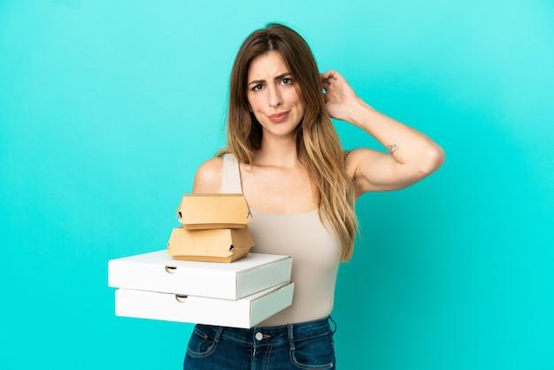 Caucasian woman holding pizzas et burger isolé sur fond bleu ayant des doutes