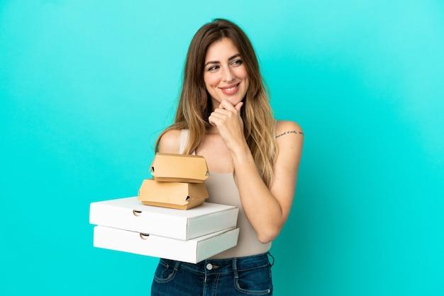 Caucasian woman holding pizzas et burger isolé sur fond bleu regardant sur le côté et souriant