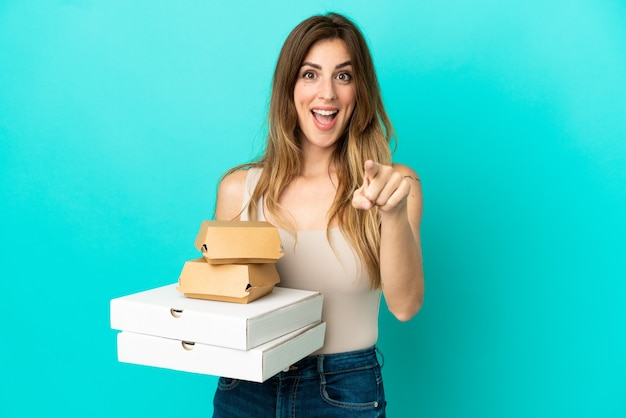 Caucasian woman holding pizzas et burger isolé sur fond bleu surpris et pointant vers l'avant