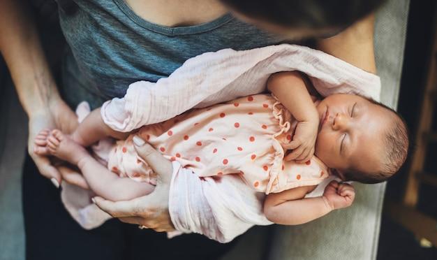 Caucasian woman holding sa fille newbord dormant dans ses mains dans une belle robe