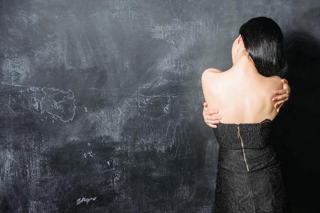 Caucasian woman in black lace dress stand avec dos sur le mur de pierre noire et se serrer dans ses bras
