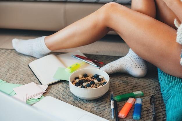 Caucasian woman sitting on floor et manger des céréales avec des baies tout en faisant ses devoirs