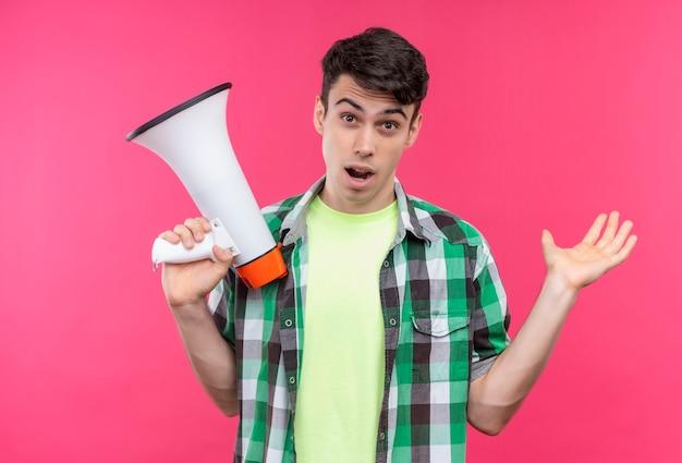 Caucasian young man wearing green shirt holding haut-parleur et main levée sur mur rose isolé