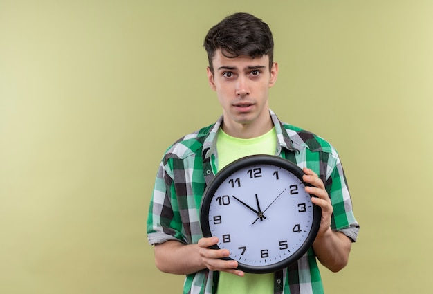 Caucasian young man wearing green shirt holding horloge murale sur mur vert isolé