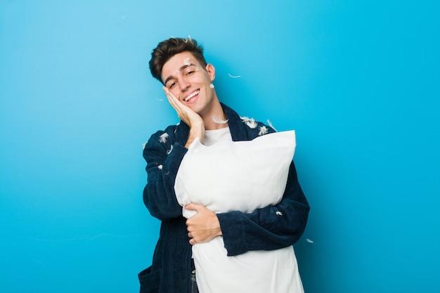 Caucasien adolescent homme fatigué tenant un oreiller