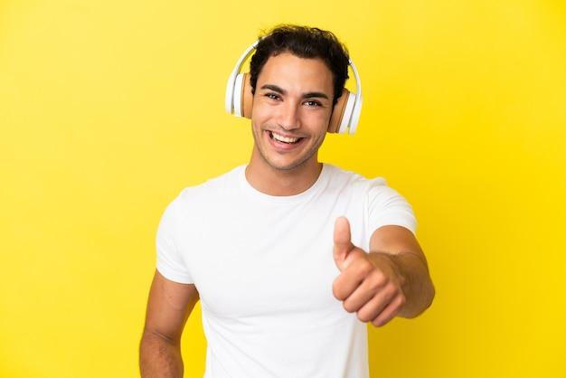 Caucasien bel homme sur fond jaune isolé, écouter de la musique et avec le pouce vers le haut