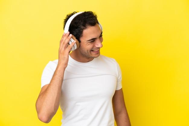 Caucasien bel homme sur fond jaune isolé, écouter de la musique