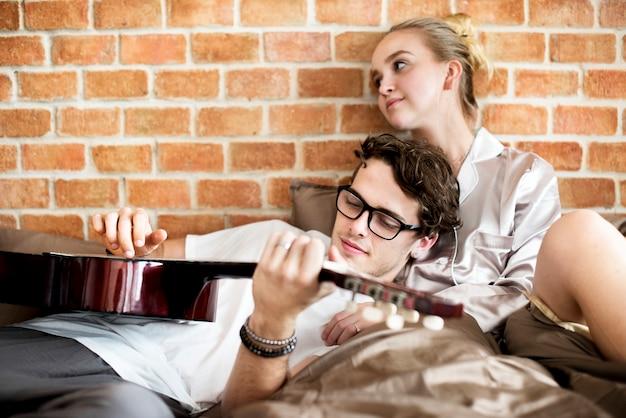 Caucasien, couple, lit, homme, guitare joue