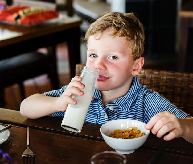 Caucasien enfant prenant son petit déjeuner seul