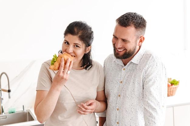 Caucasien, famille, heureux, homme femme, prendre petit déjeuner, chez soi, et, manger, croissant, sandwich