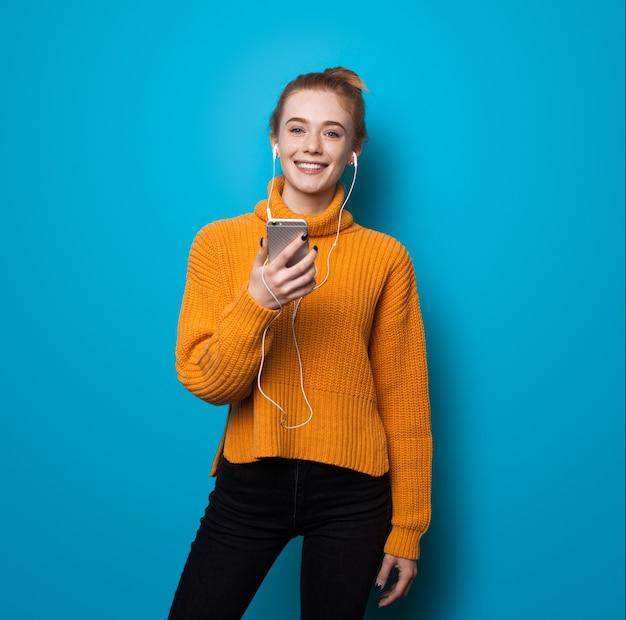 Caucasien femme au gingembre avec des taches de rousseur souriant tout en écoutant de la musique et tenant un téléphone sur le mur bleu