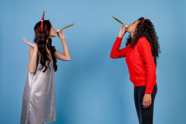Caucasien, femme, et, fille noire, souffler sifflets noël, isolé, sur, bleu