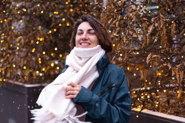 Caucasien femme souriante heureuse appréciant la neige et l'hiver, portant une écharpe chaude