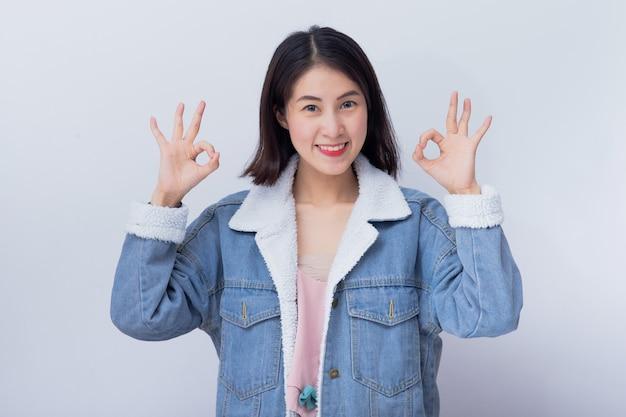 Caucasien, femme souriante, projection, main, signe ok, positif, heureux, jeune fille asiatique, porter, bleu, vêtements décontractés, portrait
