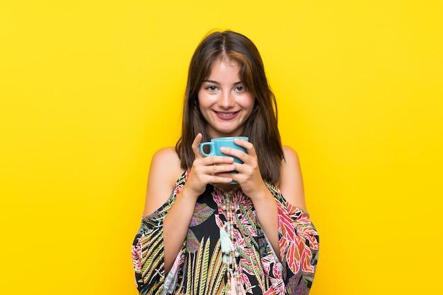 Caucasien, fille, dans, coloré, robe, sur, jaune, mur, tenue, chaud, tasse café