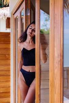Caucasien fit femme bronzée portant vintage vieux bikini, posant à la villa de l'hôtel de luxe