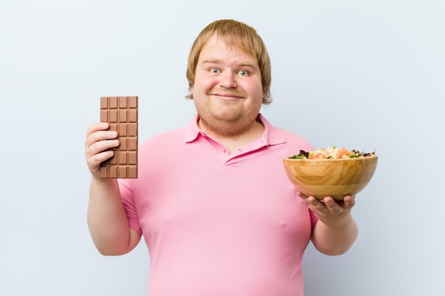 Caucasien fou blond gros homme choisissant entre une tablette de chocolat ou un saladier
