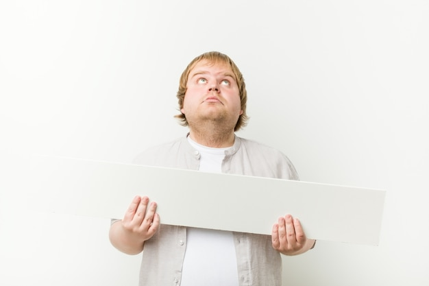 Caucasien fou blond gros homme avec une pancarte