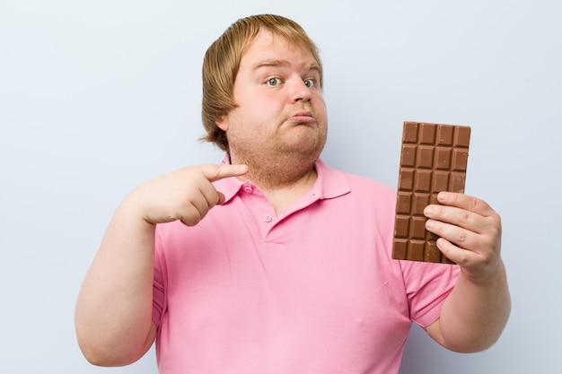 Caucasien fou gros homme blond tenant une tablette de chocolat