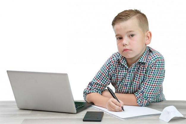 Caucasien garçon d'âge scolaire dans une chemise à carreaux assis à la table et écrit dans un morceau de papier