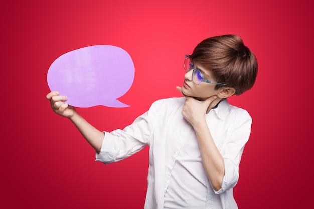 Caucasien garçon aux cheveux rouges et lunettes annonce quelque chose en regardant l'espace vide touchant le menton sur un mur rouge