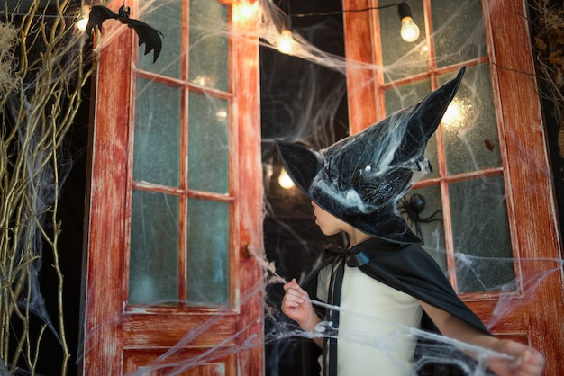 Caucasien garçon en costume de carnaval de magicien dénoue web sur un décor de halloween