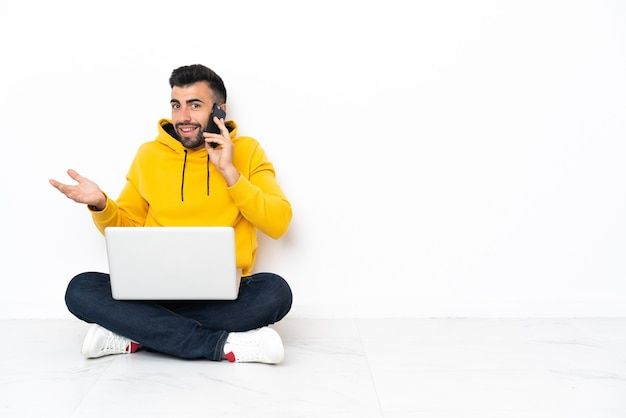 Caucasien homme assis sur le sol avec son ordinateur portable en gardant une conversation avec le téléphone mobile avec quelqu'un