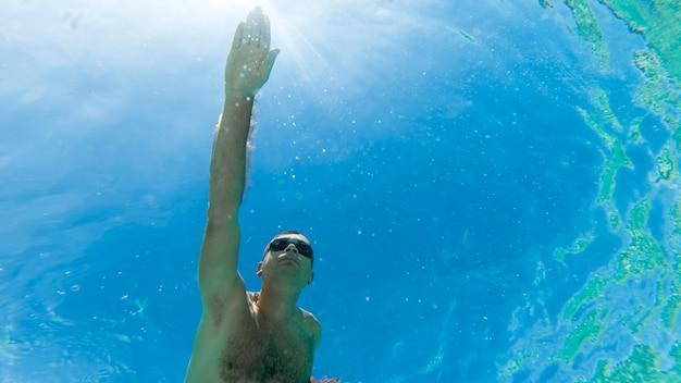Caucasien homme nager sous l'eau dans des lunettes de natation bleu eau transparente