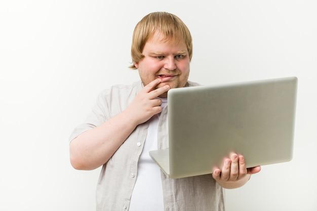 Caucasien, homme de taille plus tenant un ordinateur portable se ronger les ongles, nerveux et très inquiet.