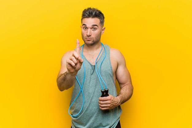 Caucasien homme tenant une corde à sauter, montrant le numéro un avec le doigt.