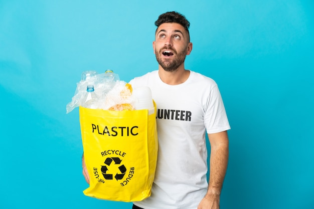 Caucasien homme tenant un sac plein de bouteilles en plastique à recycler isolé sur fond bleu en levant et avec une expression de surprise
