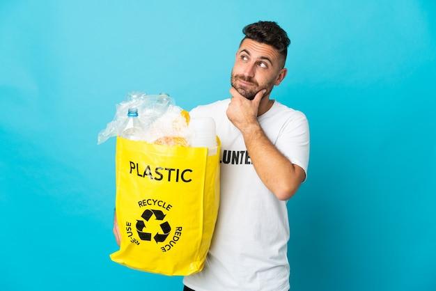 Caucasien homme tenant un sac plein de bouteilles en plastique à recycler isolé sur fond bleu et en levant