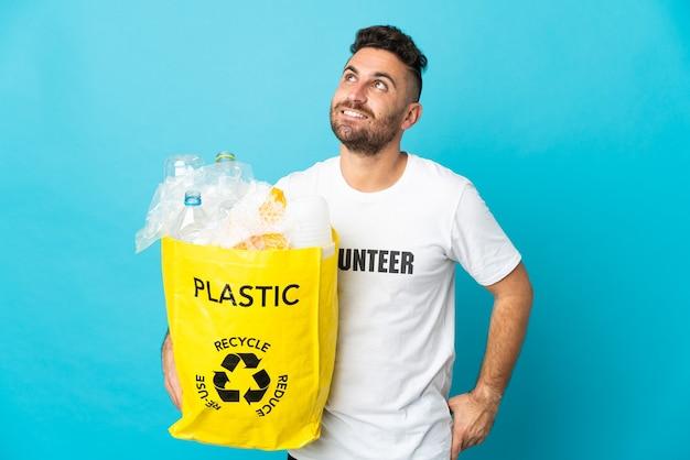 Caucasien homme tenant un sac plein de bouteilles en plastique à recycler isolé sur fond bleu en pensant à une idée tout en levant les yeux