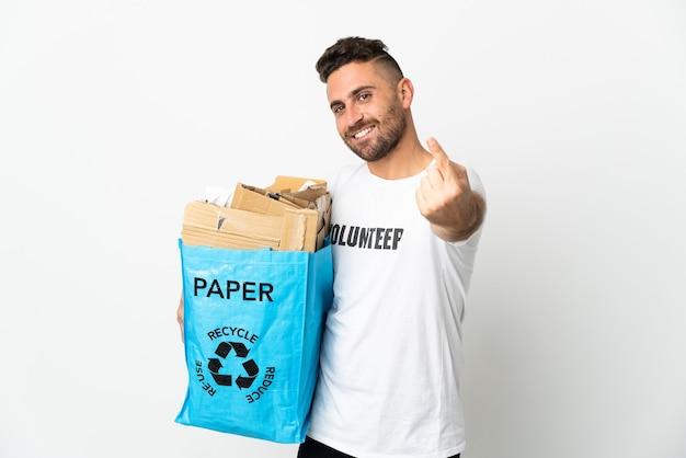 Caucasien homme tenant un sac de recyclage plein de papier à recycler isolé sur fond blanc faisant le geste à venir