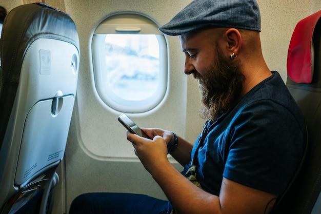 Caucasien, homme, utilisation, téléphone, avion