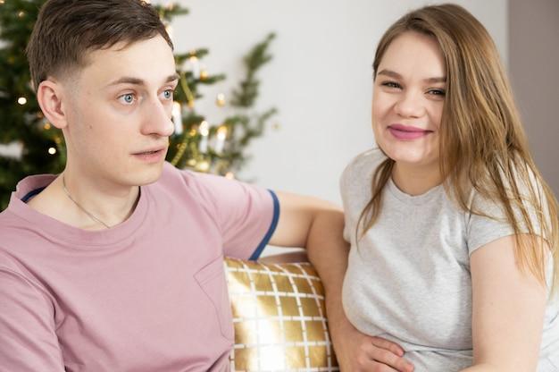 Caucasien jeune couple dans le salon. concept de grossesse, de vacances d'hiver et de personnes