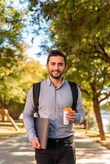 Caucasien jeune étudiant et travailleur homme buvant un café à emporter et portant son ordinateur portable dans un beau parc par une journée ensoleillée.