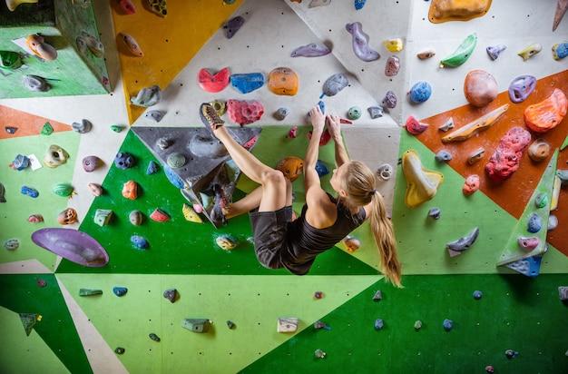 Caucasien jeune femme bouldering en salle d'escalade intérieure, prêt à faire un mouvement difficile