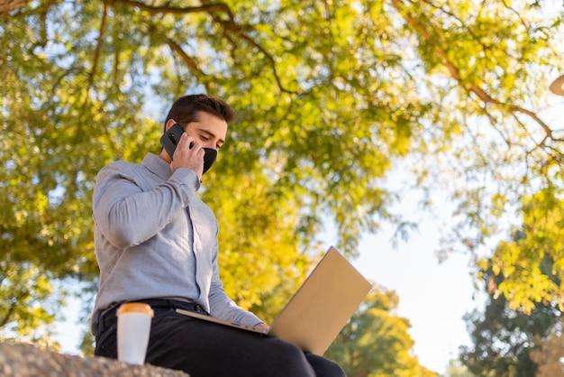 Caucasien jeune homme portant un masque facial travaillant et étudiant en ingénierie parlant au téléphone et utilisant son ordinateur portable dans un beau parc par une journée ensoleillée.