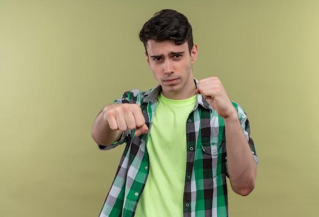Caucasien, jeune homme, porter, chemise verte, debout, dans, combat, pose, isolé, mur vert