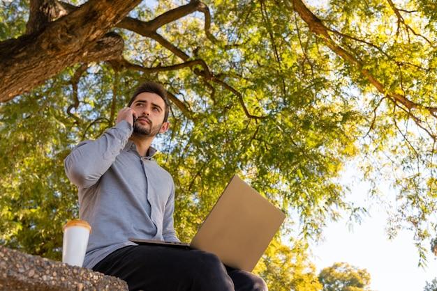 Caucasien jeune homme travaillant et étudiant en ingénierie, parler au téléphone et utiliser son ordinateur portable dans un beau parc par une journée ensoleillée.