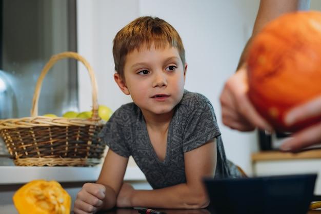 Caucasien mignon garçon de 6 ans regardant son père sculpter une citrouille pour faire une lanterne jack traditionnelle. préparation pour la fête d'halloween