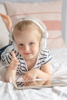 Caucasien, petite fille, dans, écoute casque, tablette, dans lit, intérieur maison, moderne, technologies appareil, style scandinave