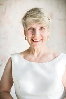 Caucasien senior femme en robe blanche joyeuse