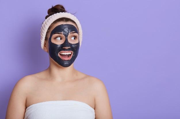 Caucasien surpris belle femme avec une serviette sur son corps avec un masque de nettoyage noir sur le visage isolé sur un mur lilas, regardant ailleurs avec la bouche largement ouverte, copiez l'espace