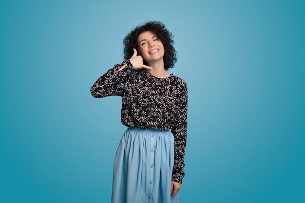 Caucasienne femme aux cheveux bouclés vêtue d'une robe bleue et posant sur un mur fait des gestes l'indicatif d'appel en souriant