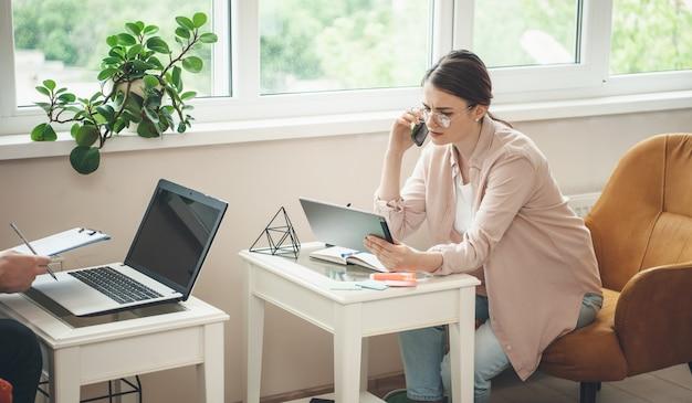 Caucasienne femme avec des lunettes parler au téléphone avec un partenaire commercial tout en regardant la tablette