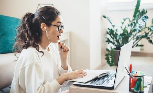 Caucasienne femme surprise après avoir vu quelque chose sur l'ordinateur portable tout en faisant ses devoirs
