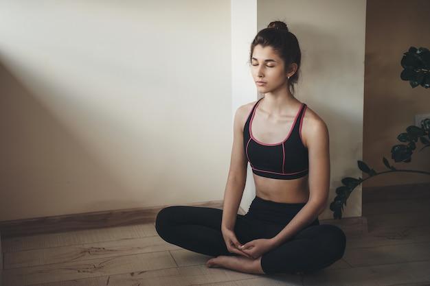 Caucasienne femme en vêtements de sport médite sur le sol tout en faisant des exercices de gym à domicile