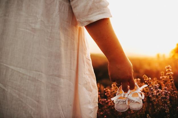Caucasienne femme vêtue d'une robe blanche pose dans un champ de blé tout en tenant une paire de chaussures de bébé